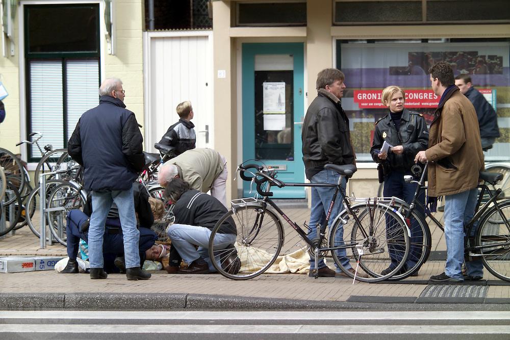 Een vrouw wordt in Groningen op straat geholpen nadat zijn met haar fiets is gevallen.<br /> <br /> A woman is being treated on the streets of Groningen after she has been having an accident with her bicycle.