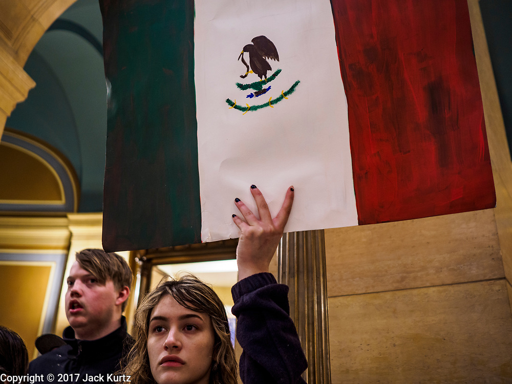 01 MAY 2017 - ST. PAUL, MN: An immigrants' rights protester holds up a Mexican flag during a May Day immigrants' rights march in the Minnesota State Capitol. About 300 people, representing immigrants' and workers' rights organizations, marched through the Minnesota State Capitol during a demonstration to mark May Day, International Workers' Day.      PHOTO BY JACK KURTZ