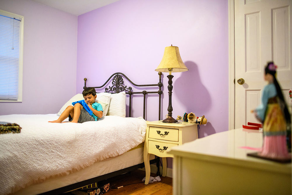 Arnold, Maryland - June 20, 2018: Nico Serrano, 4, plays on his tablet in the bedroom intended for his aunt, Delsy Guadalupe Serrano Torres, at his home in Arnold, Md., Wednesday June 20, 2018. His aunt, who goes by Lupe, and eight-year-old cousin Danny Cortes Serrano, both from Honduras, are were seeking domestic abuse asylum in the United States, but were separated at the U.S. border under the Trump Administration's Zero Tolerance immigration policy. Lupe, is in a detention center in Texas, and Danny is living with a foster family in Manhattan. <br /> <br /> Nico's mother Nila Serrano, a citizen born in Michigan, and her husband, Elnar, a U.S. resident from Honduras, are planning to sponsor Danny. Lupe was awarded a $2500 bond the day Trump signed an executive order reversing the family separation at the border. The sponsorship process, says Nila, has been exhausting.<br /> <br /> CREDIT: Matt Roth for The Wall Street Journal