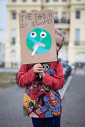 """© Licensed to London News Pictures . 22/09/2019. Brighton, UK. A girl holds a placard reading """" The earth is poorly """" . Environmental campaigners from Extinction Rebellion highlight the climate emergency and deploy a large red and white lighthouse lightship named """" Greta """" , on Brighton Promenade , during the second day of the 2019 Labour Party Conference from the Brighton Centre . Photo credit: Joel Goodman/LNP"""