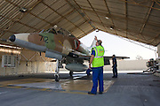 Israeli Air Force Mcdonnell-Douglas Skyhawk fighter jet on the ground directed by ground crew into a maintenance hangar