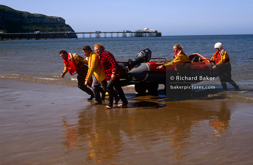Volunteer RNLI lifeboatmen bring ashore one of their inflatable dinghies on to the beach at Llandudno, Wales. Wearing wetsuits, they drag the small outboard using a trailer on wheels and will return it to the beach hut on shore.