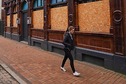 © Licensed to London News Pictures. 2/03/2021. Sheffield, UK. A member of the public walks past a boarded up pub in Sheffield during the third lockdown.  .Photo credit: Ioannis Alexopoulos/LNP