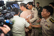 "23 JANUARY 2013 - BANGKOK, THAILAND:  SOMYOT PRUESAKASEMUK (center, orange jump suit) is led to a waiting pickup truck after sentencing Wednesday. Somyot was sentenced to 11 years imprisonment Wednesday for violations of Thailand's ""Lese Majeste"" laws. He was arrested on April 30, 2011, and charged under article 112 of Thailand's penal code, which states that ""whoever defames, insults or threatens the King, the Queen, the Heir-apparent or the Regent, shall be punished with imprisonment of three to fifteen years"" after the magazine he edited, ""Red Power"" (later changed to ""The Voice of Thaksin"") published two articles by Jit Pollachan, the pseudonym of Jakrapob Penkair, the exiled former spokesman of exiled fugitive former Prime Minister Thaksin Shinawatra. Jakrapob, now living in Cambodia, has never been charged with any crime for what he wrote.      PHOTO BY JACK KURTZ"