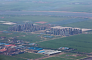 A view of a vast housing development rising up from the middle of farmland seen from an airplane near Tianjin, China on 16 July 2013. Despite continued government efforts to cool the property market, housing prices across China continue to grow rapidly.