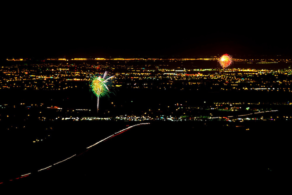 View of Front Range July 4th fireworks displays from the Flatirons above Boulder, Colorado.