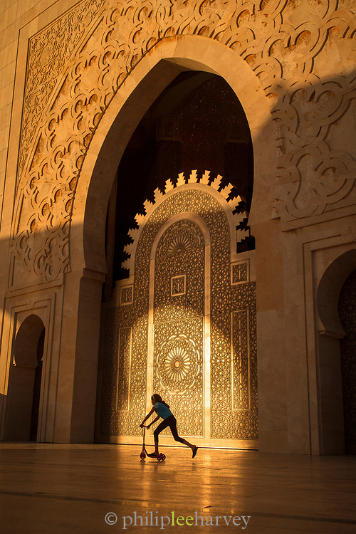 Side view of girl on scooter by Hassan II Mosque in Casablanca, Morocco
