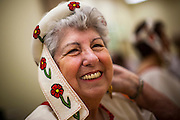 27 JUNE 2012 - GLENDALE, AZ:  HELENA ROER, 75 years old, puts on her outfit before a dress rehearsal for the Senior Fiesta Dancers at the Glendale Adult Center, in Glendale, AZ, a suburb of Phoenix. Dancing as a part of workout regimen is not unusual, but the Senior Fiesta Dancers use Mexican style folklorico dances for their workouts. The Senior Fiesta Dancers have been performing together for 15 years. They get together every week for rehearsals and perform at nursing homes and retirement centers in the Phoenix area once a month or so. Their energetic Mexican folklorico dances keep them limber and provide a cardio workout.   PHOTO BY JACK KURTZ