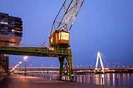 old crane in the Rheinau harbour, in the background the Severins bridge, Cologne, Germany.<br /> <br /> alter Kran im Rheinauhafen, im Hintergrund die Severinsbruecke, Koeln, Deutschland.