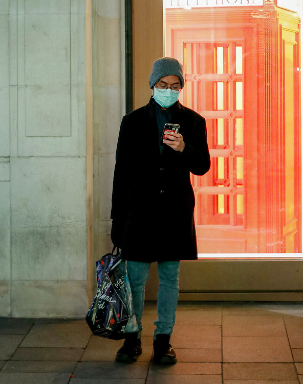 A man checks his phone on Regent Street, London after the 2nd National Lockdown was lifted.