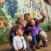 """Brian Gilstrap takes a selfie with his wife Annie, and children Hayes, 3, and Collins, 2, at a mural behind his ETX Brewing Company in Tyler, Texas. The """"be happy"""" mural is a take on the brewery's slogan of """"beer, happy."""" Nathan Lambrecht/Journal Communications"""