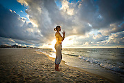 A woman does yoga on the beach at sunrise.