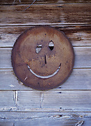 Smiling face cut from the lid of a 55-gallon drum decorating the side of an outhouse in Levan, Utah.