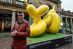 © Licensed to London News Pictures. 07/10/2021. LONDON, UK. Artist Whatshisname (real name Sebastian Burdon) poses with his work Downward Balloon Dog installed in Covent Garden. In total, four colourful balloon dogs are on display until the end of October.  The public are encouraged to take photos and post them to social media with a hashtag #castleforbluecross and Castle Fine Art will donate £1 to the Blue Cross animal welfare charity for each post..  Photo credit: Stephen Chung/LNP