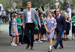The Duke of Sussex walks with a pupil during a visit to Albert Park Primary School in Melbourne, on the third day of the royal couple's visit to Australia.