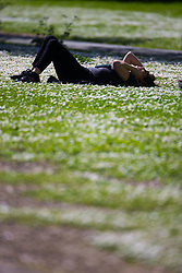 A woman lies among the daisies soaking up the sun on a perfect spring day in Regents Park. London, May 04 2018.