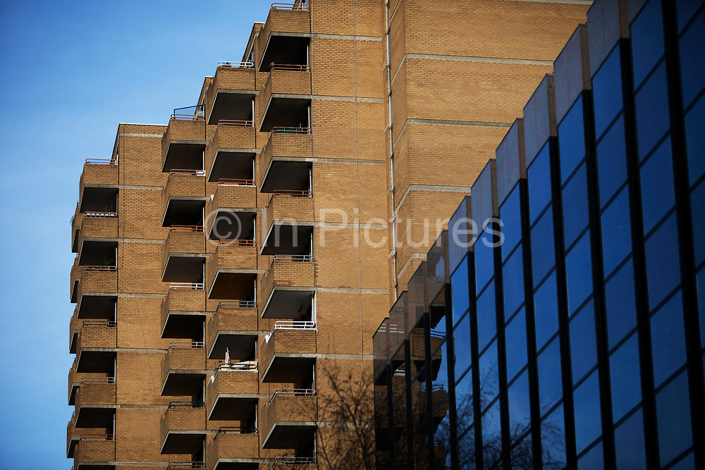 Balconies of some council flats in Holborn, London. The apartments contrast with a glass covered office building it is next to.