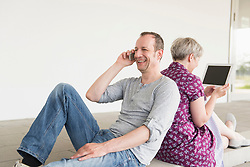 Mature man talking on cell phone and mature woman using digital tablet, smiling