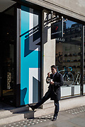 A man eats his lunchtime sandwich outside cycling retailer Pinarello, on 25th February 2019, in London, England.