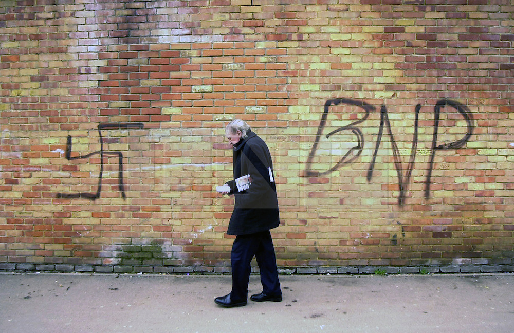 © Licensed to London News Pictures 04/05/2004.A man walks past BNP and right wing graffiti on a wall in Craylands estate, an impoverished council estate in Basildon, Essex..Basildon, UK.Photo credit: Anna Branthwaite