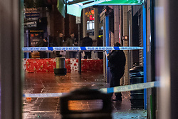 © Licensed to London News Pictures. 13/12/2020. London, UK. A police officer stands inside a cordon marked off by police tape on Station Road, Police were called at approximately 19:15GMT on Sunday, 13 December to reports of a stabbing in St Anns Road, Harrow. Officers and London Ambulance Service attended. <br /> A man – believed aged in his 20s – was found suffering stab injuries; despite the efforts of the emergency services he was pronounced dead at the scene. Two further males – both believed aged in their late teens – also suffered stab injuries. Photo credit: Peter Manning/LNP