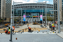 © Licensed to London News Pictures. 15/04/2021. LONDON, UK.  Construction workers laying paving in front of the soon to be completed Olympic Steps leading up to Wembley Stadium.  The 48 Olympic Steps comprises 4 flights of 12 steps and will become the new gateway to the stadium for visitors and fans arriving from Olympic Way and is due to be completed in June 2021 in time for England group stage matches at Euro 2020.  Photo credit: Stephen Chung/LNP