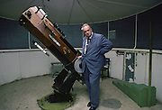 Astronomer Sir Patrick Moore with his telescope in his own Observatory at home in Sussex, England