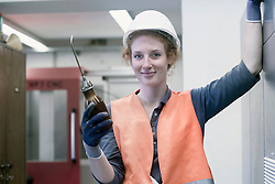 Female engineer holding oil flask in workshop, Freiburg im Breisgau, Baden-Wuerttemberg, Germany