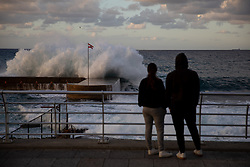 © Licensed to London News Pictures. 15/01/2021. Beirut, Lebanon. People look out to sea on the Corniche in Beirut, which is near empty on the second day of an 11 day curfew (from 14 Jan to 25 Jan) in an attempt to control a rapid increase in rates of COVID-19 Coronavirus in the country. Today, Lebanon registered two record-breaking statistics, with 6154 cases of Coronavirus, and 44 deaths in the past 24 hours. Photo credit : Tom Nicholson/LNP