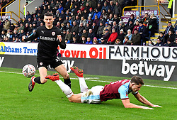 Barnsley's Kieffer Moore (left) and Burnley's James Tarkowski (right) battle for the ball during the Emirates FA Cup, third round match at Turf Moor, Burnley.