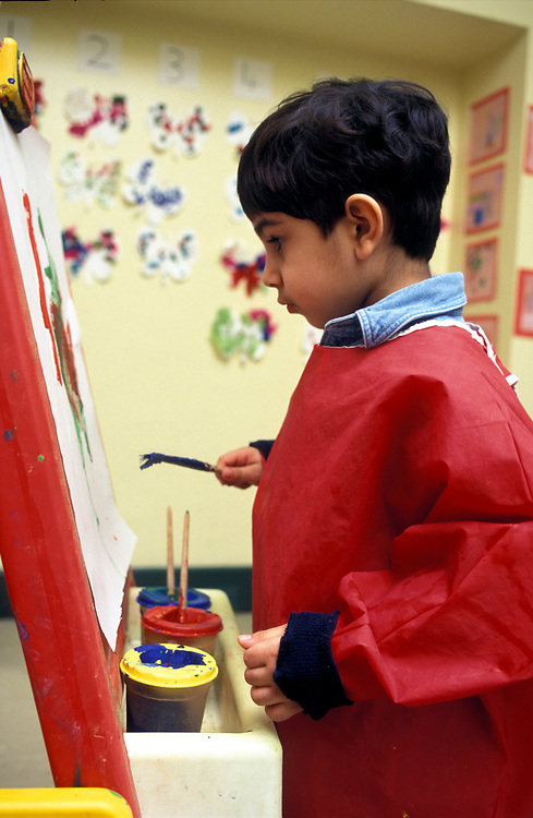 Young Asian child painting at an easel in primary school