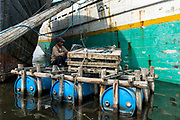 Indonesian man<br /> Painting ship<br /> Harbour<br /> Jakarta<br /> Indonesia