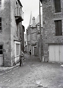 male person standing with view of narrow street 1930s