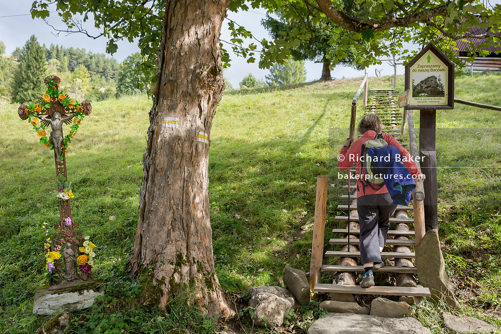 A walker climbs wooden steps in Biala Woda in the Tatra mountains, passing a sheet metal Jesus crucifix (a popular local copy from an historical Rutherian church) near Jaworki, on 20th September 2019, near Szczawnica, Malopolska, Poland. The village of a thriving Rutherian community was once here in Biala Woda where over 100 farms were located - the remains of which are still seen. A wooden cross with a figure of Christ cut from sheet metal survived the culture. Similar crosses and chapels can be found in the colloquial language of White Water  in the Romanian, Ukrainian or Eastern Slovakia Carpathians.
