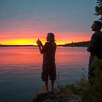 Campers admire a sunset over Lake of the Woods, Ontario, Canada.