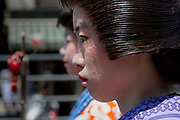 Young girls dressed as geisha walk ahead of a mikoshi procession during the Sanja matsuri, Asakusa, Tokyo, Japan. Sunday May 21st 2017 . The Sanja matsuri (Three shrines festival) is one of the biggest Shinto festivals in Japan. It takes place for 3 days around the third weekend of May and features over 100 large and small mikoshi, or portable shrines, which are paraded around the streets of the historic Asakusa district in Tokyo. to bring blessings and good luck on the inhabitants. The events attracts up to 2 million visitors each year.