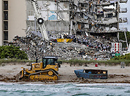 A bulldozer pulls a migrant boat that washed ashore in Surfside as search and rescue teams look for survivors at the 12-story oceanfront condo, Champlain Towers South, on Tuesday, June 29, 2021.