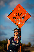 """SHOT 2/16/19 5:04:15 PM - Vesta Lingvyte of Denver, Colo. poses under a """"Stay Present"""" sign along the beach road in Tulum, Mexico. Tulum (sometimes Tulum Pueblo) is the largest community in the municipality of Tulum, Quintana Roo, Mexico. It is located on the Caribbean coast of the state, near the site of the archaeological ruins of Tulum. The community had a 2010 census population of 18,233 inhabitants. As recently as the early 1990s Tulum Pueblo was a quiet village about 2 miles from the archaeological site, and tourism outside of the ruins was limited to a few small shops and simple cabanas on the beach. More recently the """"hotel zone"""" of boutique hotels along the Tulum beach has grown to more than 70 small hotels with an upscale bohemian vibe to many of the properties. (Photo by Marc Piscotty / © 2019)"""