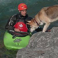 Kayaker Paul Manning-Hunter Manning briefly greets his dog beside  the Kananaskis River near Calgary, Alberta, Canada.