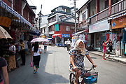 Street scene near Yu Yuan Garden in Shanghai, China. A woman cycles past trying to keep cool in the heat.