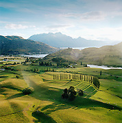 View across farmland towards lakes and Southern Alps from helicopter, Queenstown, Southern Alps, South Island, New Zealand.