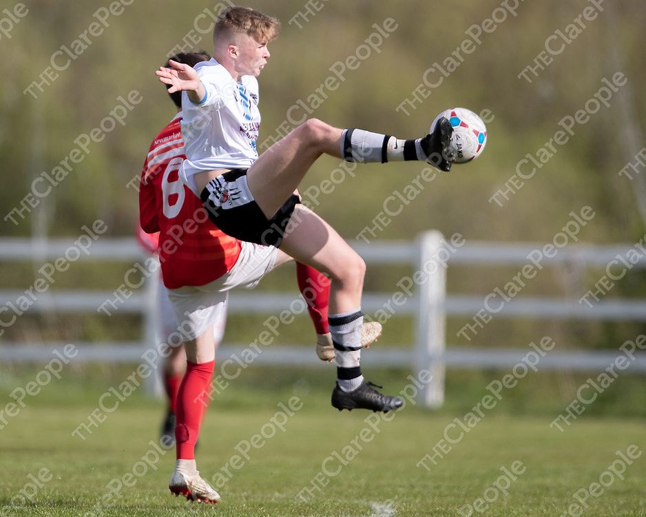 Manus Celtic's Dylan Browne jumps for the ball while under pressure from Newmarket Celtic's Callum Hussey