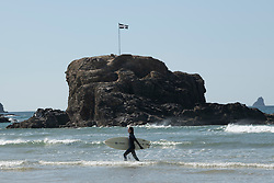 © Licensed to London News Pictures. 04/04/2020. Surfer walks past Chapel Rock after surfing. Surfing at Perranporth beach during the coronavirus lockdown. Cornwall UK. . Photo credit: Mark Hemsworth/LNP