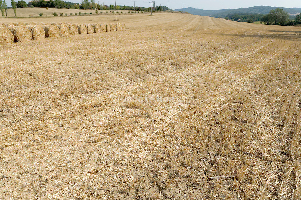 French landscape with bales of straw and tractor tracks on harvested field