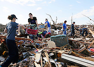 A line of volunteers forms a chain to retrieve clothing at a tornado-destroyed home across the street from the Plaza Towers elementary school in Moore, Oklahoma May 22, 2013. A massive tornado tore through a suburb of Oklahoma City, wiping out whole blocks and killing at least 24.   REUTERS/Rick Wilking (UNITED STATES)