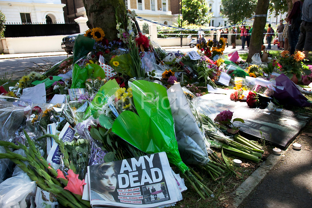A newspaper headline reads 'AMY DEAD' as people gather and lay flowers at a memorial opposite the home of Amy Winehouse, Camden Square, North London. It was announced that the tragic singer had died on 23rd July 2011. The music world has been paying tribute to singer Amy Winehouse, 27, who was found dead at her London home following years of drug and alcohol abuse largely attributed to her troubled character and fame.