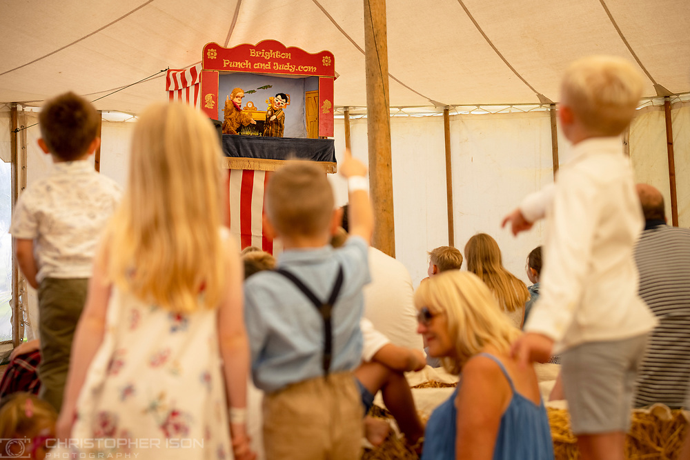 Children watch a Punch & Judy show at Goodwood Racecourse.<br /> Picture date: Saturday August 28, 2021.<br /> Photograph by Christopher Ison ©<br /> 07544044177<br /> chris@christopherison.com<br /> www.christopherison.com<br /> <br /> IMPORTANT NOTE REGARDING IMAGE LICENCING FOR THIS PHOTOGRAPH: This image is supplied to the client under the terms previously agree. No sales are permitted unless expressly agreed in writing by the photographer.
