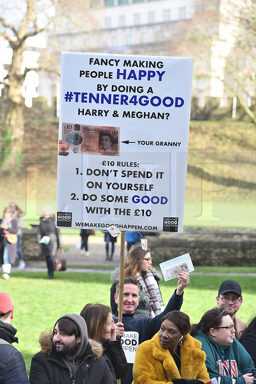 ©Licenced to London News Pictures. 18/01/2018. Cardiff, Wales, UK. Crowds at Cardiff Castle wait for Prince Harry and Meghan Markle on their first official visit to Wales since announcing their engagement. Matt Callanan holds up a placard asking if the royal couple will participate in his good deeds scheme tenner for good. The prince and his intended will tour a cultural festival at the historic site. Photo credit IAN HOMER/LNP