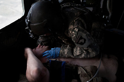"""A flight medic leans in to hear the words spoken by a Canadian soldier who has just lost his left foot to an IED strike in western Kandahar province. Scenes from the medical evacuations of wounded Americans, Canadians, and Afghan civilians and soldiers being flown by Charlie Co. 6th Battalion 101st Aviation Regiment of the 101st Airborne Division. Charlie Co. - which flies under the call-sign """"Shadow Dustoff"""" - flies into rush the wounded to medical care out of bases scattered across Oruzgan, Kandahar, and Helmand Provinces in the Afghan south. These images were taken of missions flown out of Kandahar Airfield in Kandahar Province and Camp Dwyer in Helmand Province."""