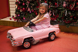 © Licensed to London News Pictures. 27/06/2013. London, UK. Lottie, 5, sits in a Hollywood Pedal Car (Hamleys price GB£250) at the Christmas in June press event at Hamleys toy shop in London today (27/06/2013).  Held in retailers world famous Regents Street store, the event showcases the predicted top toys for Christmas 2013. Photo credit: Matt Cetti-Roberts/LNP